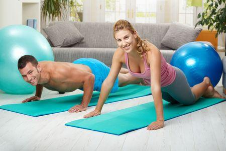 BUEN VIVIR: Joven pareja haciendo empuje ejercicio en casa, en la sala de estar.
