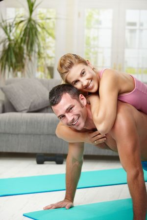 men exercising: Joven pareja haciendo empuje ejercicio en casa, en la sala de estar.