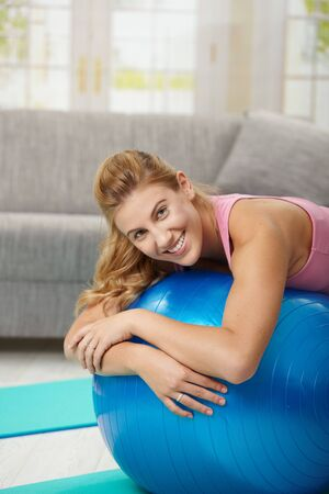 Young woman lying on fit ball at home, smiling. photo