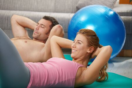 Young couple doing abdominal crunch lying on fitness mat at home in living room. photo