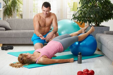 Young couple doing abdominal exercise with fit ball in living room, smiling. photo