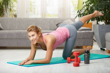 Young woman doing leg exercises lying on fitness mat in living room, smiling. Stock Photo - 6026636