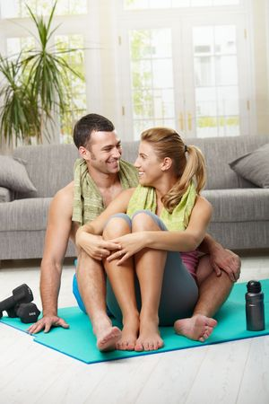 snug: Happy couple resting after training, sitting on fitness mat in living room, looking at each other smiling. Stock Photo