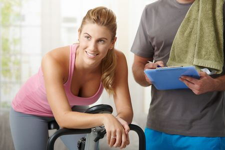home trainer: Young woman training on exercise bike with personal trainer at home, smiling.