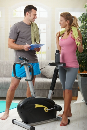 snug: Young woman talking with her personal trainer standing beside exercise bike at home.