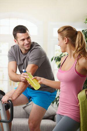 Man training on exercise bike at home, listening music. photo