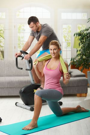 exercise room: Man training on exercise bike, woman doing streching exercise on fitness mat at home. Stock Photo