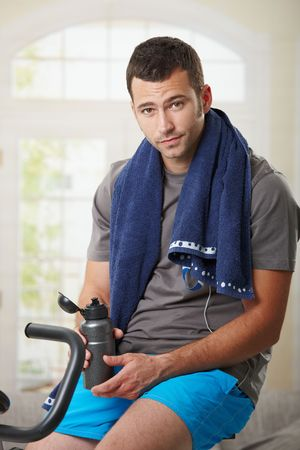 snug: Tired man sitting on stationary bike and resting after training.