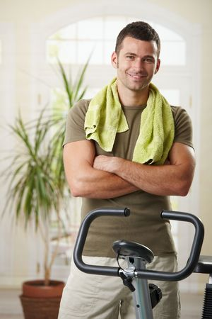 Man wearing sportswear and towel standing in living room at home with training bike, smiling. Stock Photo - 6026644