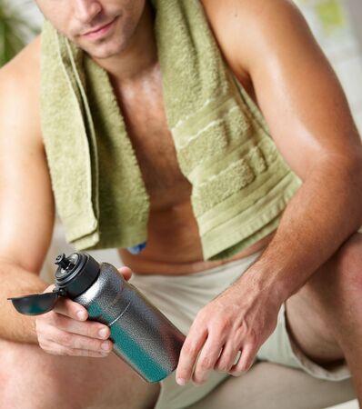 Cansado hombre descansando despu�s de la formaci�n, celebraci�n de botella en la mano. Selectiva se centra en la botella. Foto de archivo - 6026632