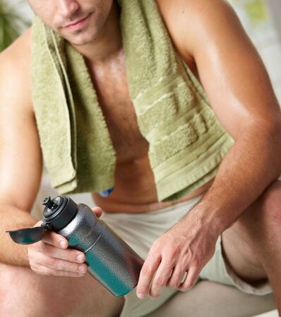 Tired man resting after training, holding bottle in hand. Selective focus on bottle. Stock Photo - 6026632