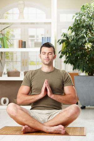 Man doing yoga exercise at home, sitting on floor in living room. photo