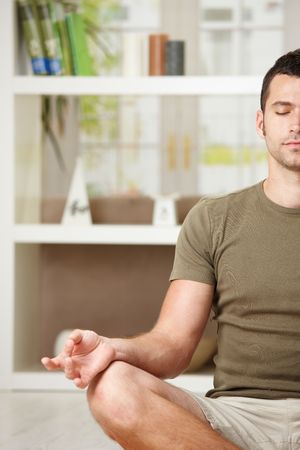 BUEN VIVIR: Hombre haciendo ejercicios de yoga en casa, sentada en el suelo en la sala de estar, retrato de la mitad.