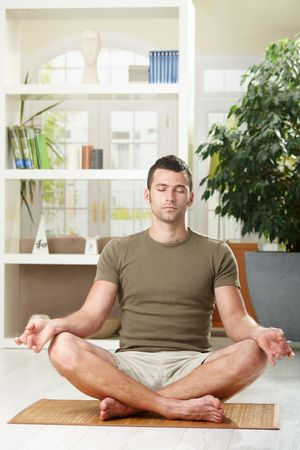 yoga man: Man doing yoga exercise at home, sitting on floor in living room.