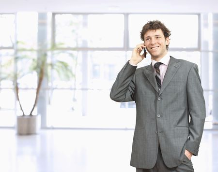 Young businessman standing in office lobby with hand in pocket, talking on mobile phone, smiling. Stock Photo - 6041157