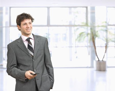businessman waiting call: Young businessman standing in office lobby with hand in pocket, using mobile phone, smiling.