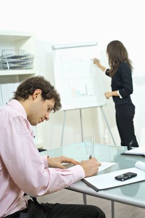 Young businessman sitting at desk, writing notes. Businesswoman standing in background, drawing chart on whiteboard. Selective focus on man. photo