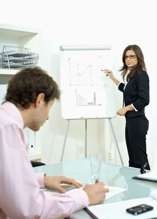 Young businessman sitting at desk, writing notes. Businesswoman standing in background, drawing chart on whiteboard. Selective focus on woman. photo