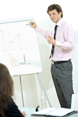 finacial: Young businessman wearing pink shirt standing at in office , drawing and explaining finacial chart on whiteboard.