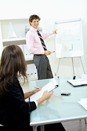 Young businesswoman sitting at desk, writing notes. Businessman standing in background, drawing chart on whiteboard. Selective focus on man. Stock Photo - 6041052