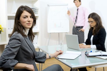 Young businesswomen sitting at desk, writing notes. Businesswoman standing in background, drawing chart on whiteboard. Selective focus on woman in front. photo