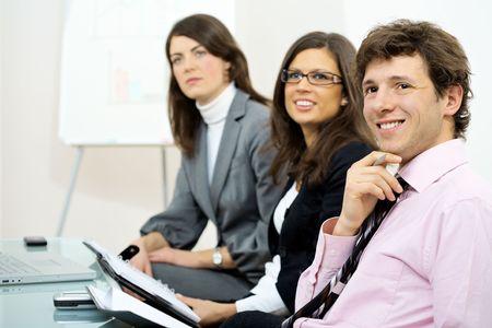 together with long tie: Grupo de empresarios sentado en la fila en la formaci�n y mirando el entrenador positivamente una sonrisa.