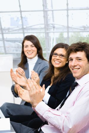 Group of smiling businesspeople sitting in row on training and clapping. Stock Photo - 6041047