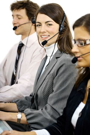 Young customer service operators sitting in a row and talking on headset, smiling.