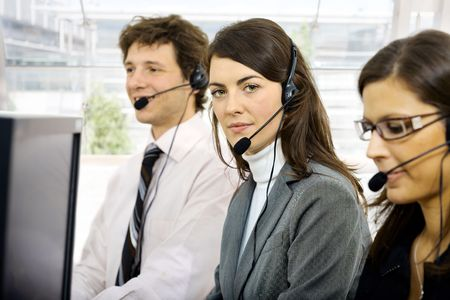 Three young customer service operators sitting in a row and talking on headset. Selective focus on women in middle. Isolated on white background. photo