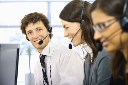 Young customer service representatives sitting in a row and talking on headset, smiling. Selective focus is placed on man. photo