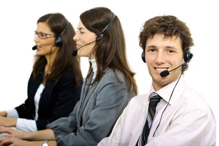 Happy customer service representatives sitting in a row and talking on headset, smiling. Isolated on white background. photo