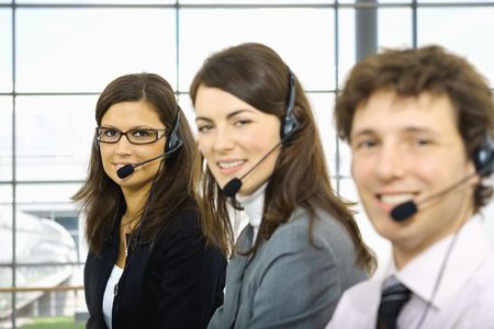 Team of  young customer service operators sitting in a row and talking on headset. Selective focus on women in middle. photo