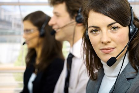 Three young customer service operators sitting in a row and talking on headset. Selective focus on women in front. photo