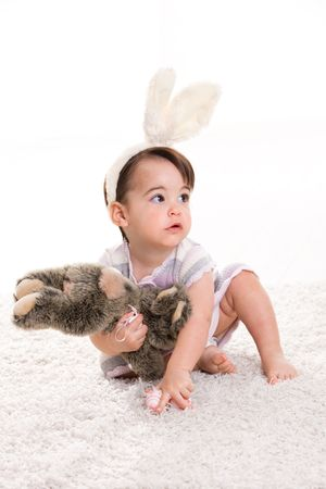 Baby girl in easter bunny costume, playing with toy rabbit, isolated on white background. photo