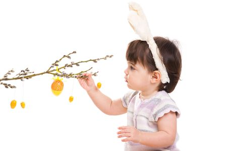 Baby girl in easter bunny costume, playing with easter eggs hanging from willow branch. Isolated on white background. Stock Photo - 6220031