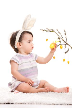 Baby girl in easter bunny costume, playing with yellow easter egg decoration. Isolated on white background. photo