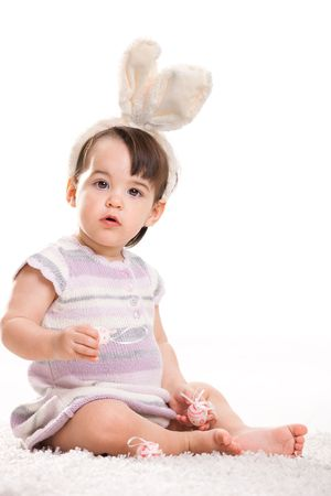 Baby girl with bunny ears headband, playing with easter eggs, isolated on white background. photo