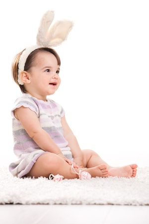 Happy baby girl in easter costume sitting on carpet, laughing. Isolated on white background. Stock Photo - 6220039