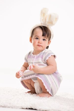 Baby girl with bunny ears headband, crouching on carpet, playing with easter eggs, smiling. Isolated on white background. Stock Photo - 6220029