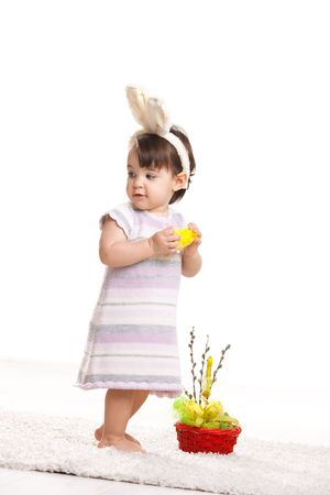 Baby girl in easter bunny costume, standing beside easter basket and holding toy chicken, looking back. Isolated on white background. photo