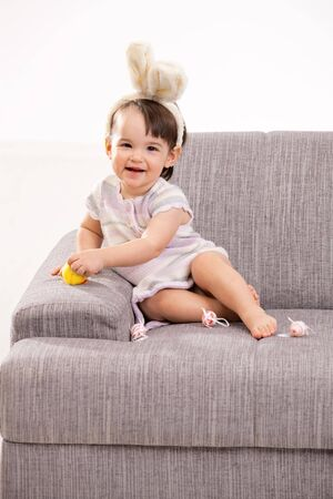 Baby girl in easter bunny costume, sitting on grey couch playing with toy chicken and easter eggs, laughing. Isolated on white background. Stock Photo - 6220034