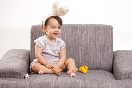 Baby girl in easter bunny costume, sitting on grey couch playing with toy chicken and easter eggs, laughing. Isolated on white background. photo