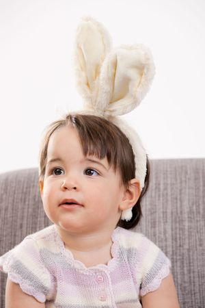Closeup portrait of baby girl in easter bunny costume, sitting on grey couch. Isolated on white background. Stock Photo - 6220060