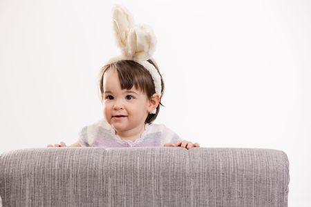 Portrait of baby girl in easter bunny costume, smiling. Isolated on white background. photo