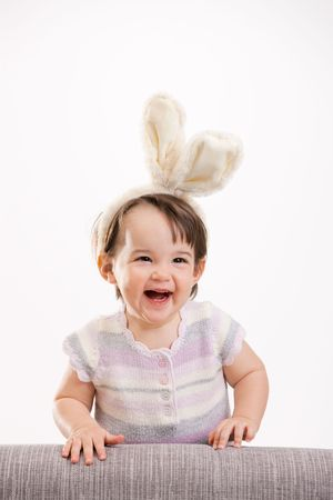 Closeup portrait of happy baby girl in easter bunny costume, laughing. Isolated on white background. photo