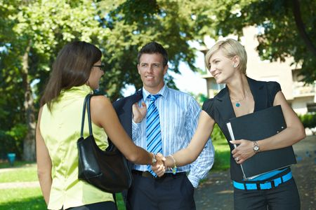 person outside: Young businesspeople meeting in park, shaking hands. Stock Photo