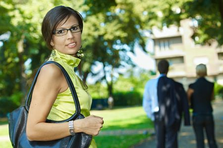 Portrait of young woman standing in sunny park, smiling. Stock Photo - 6220682