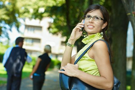 Young businesswoman talking on mobile phone outdoor in a park. photo