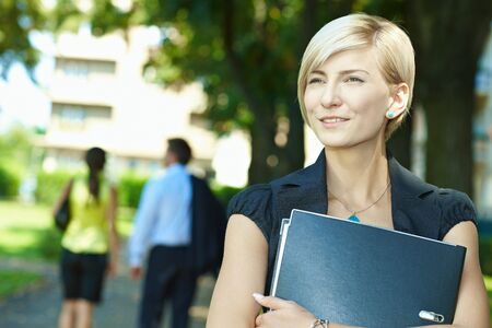 Portrait of young woman standing in sunny park, smiling. Stock Photo - 6220058
