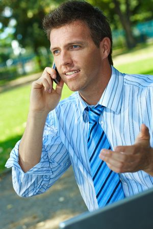 Businessman working outdoor in park, using laptop and talking on mobile. Stock Photo - 6220025